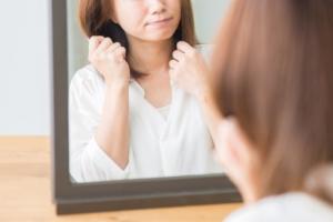 鏡の自分を励ます女性